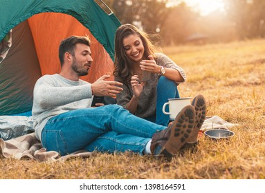 Happy young couple sitting by tent at campsite spending time together in nature.