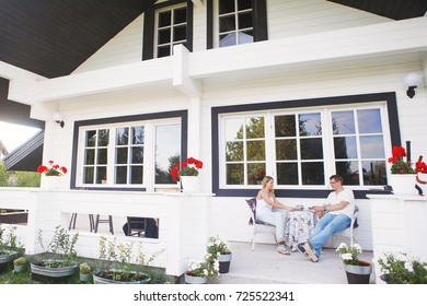 Happy young couple sitting and drinking tea on the porch