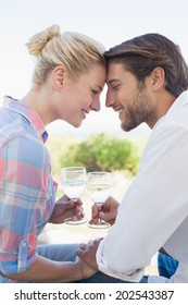 Happy young couple sitting in the garden enjoying wine together on a sunny day