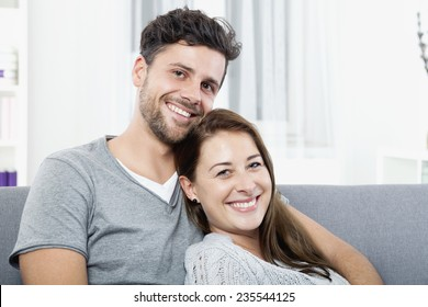 Happy young couple sitting at home on couch