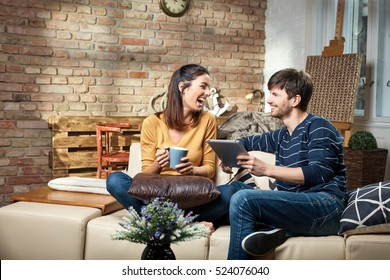 Happy young couple sitting at home on sofa, using tablet, smiling happy.