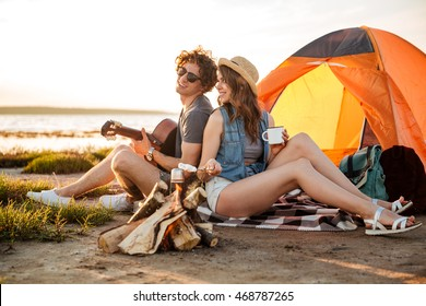 Happy young couple sitting near campfire and playing guitar