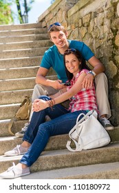 Happy young couple sitting on stone stairs smiling together outdoors