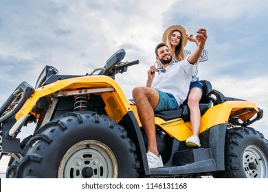 happy young couple sitting on ATV and taking selfie