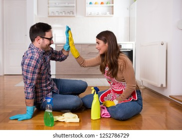 Happy young couple sitting on floor after housekeeping and doing give me five gesture