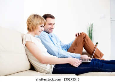 Happy young couple sitting on couch using laptop