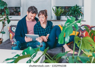 happy young couple sitting on the sofa and watching on a tablet