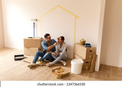 Happy young couple sitting on the ground making a break from moving-in in their new apartment while man holding tape in his hands. holding