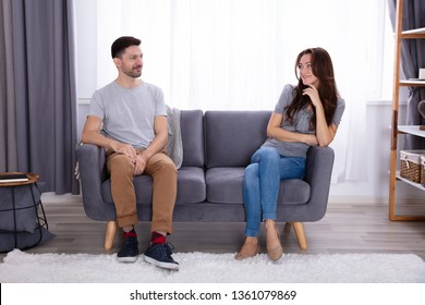 Happy Young Couple Sitting On Sofa Looking At Each Other