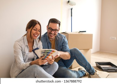 Happy young couple sitting on the ground smiling while trying to choose color from color palette for walls in their new apartment.