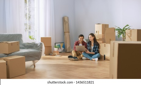 Happy Young Couple Sitting on the Floor of the Newly Rented / Purchased Apartment Use Laptop Computer. Unpacked Cardboard Boxes and Covered Furniture in the Modern Bright Sweet Home.
