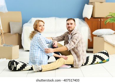 Happy young couple sitting on floor in their new flat