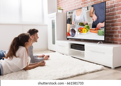 Happy Young Couple Sitting On Sofa Watching Recipe On Television At Home