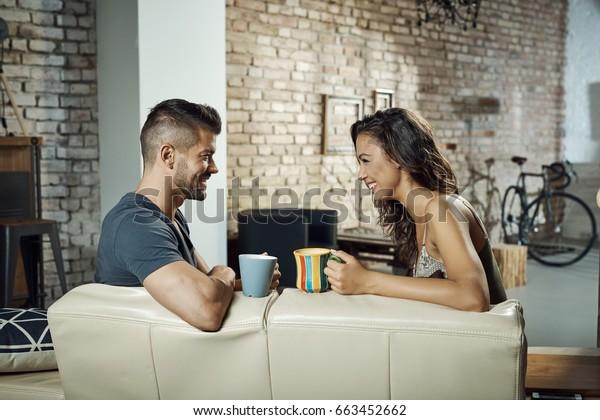 幸せな若い夫婦がソファに座り、話し、笑い、お茶を飲む。側面図。