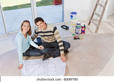 Happy young couple sitting together with blueprint and color buckets in the background