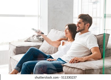 Happy young couple sitting and watching TV at home