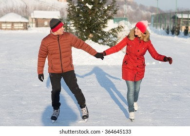 Happy young couple skating at the rink in the winter. A couple walking and playing on the ice in winter sunny day.