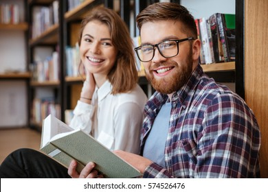 Happy young couple smiling and reading book in library