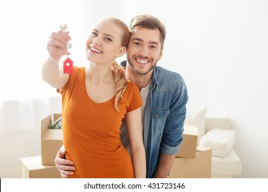 Happy young couple smiling while holding key from house