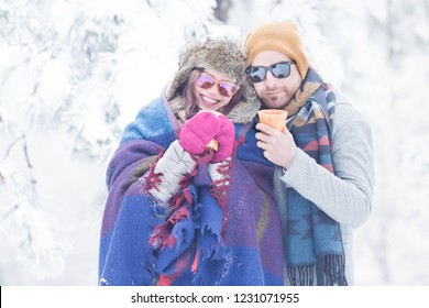 Happy young couple in snow outdoors with coffee