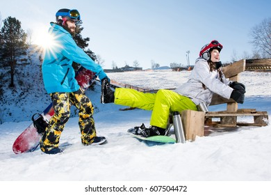 Happy young couple of snowboarders fooling aroung at ski resort
