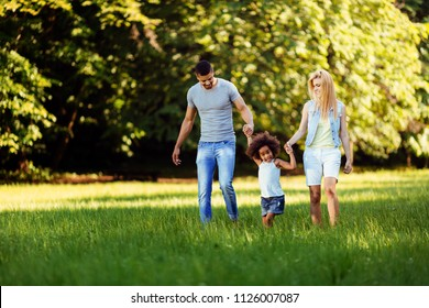 Happy young couple spending time with their daughter