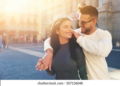 Happy young couple is spending vacation holidays in Barcelona city. Both look really happy. They are strolling along the streets of the old town and hanging out with pleasure, seeing attractions.