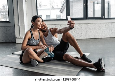 happy young couple in sportswear taking selfie with smartphone while resting on yoga mats after workout in gym