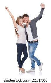 Happy young couple standing close together in a loving embrace celebrating and laughing punching the air with their raised fists on white