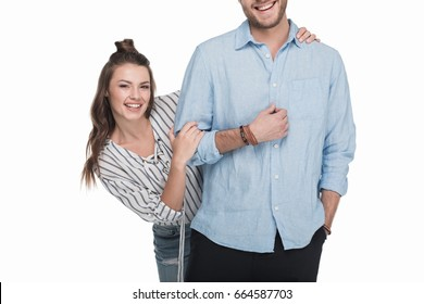 Happy young couple standing embracing and smiling at camera isolated on white