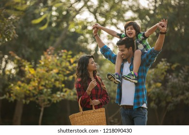 Happy young couple standing in a garden with the man carrying their son on his shoulders and the woman carrying a basket