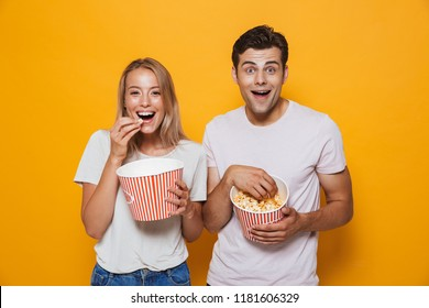 Happy young couple standing isolated over background, eating popcorn