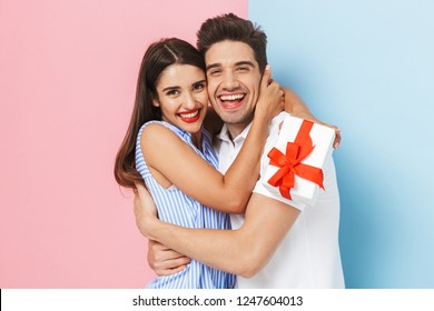 Happy young couple standing isolated over two colored background, celebrating, holding gift box, hugging