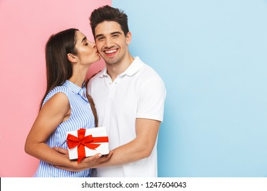 Happy young couple standing isolated over two colored background, celebrating, holding gift box, kissing