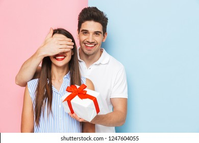 Happy young couple standing isolated over two colored background, celebrating, holding gift box