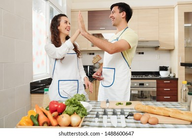 Happy young couple standing at kitchen table in aprons and giving each other high five
