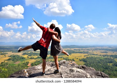 Happy young couple standing on the rock taken at hanging rock, Phayao, Thailand Taken date November 24, 2018 Dressing Muangthong shirt (have Coca Cola, AIA, Toshibah on) Nike pants and Nike shoes