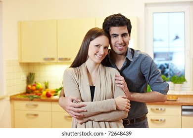 Happy young couple standing in their new kitchen