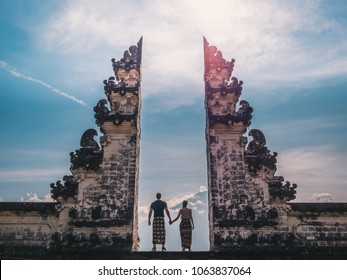 Happy young couple staying in temple gates of heaven and holding hands of each other. Perfect Honeymoon concept.  Lempuyang Luhur temple in Bali, Indonesia.