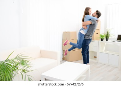 happy young couple student roommate packing boxes and moving furniture during their move into new home flat apartment
