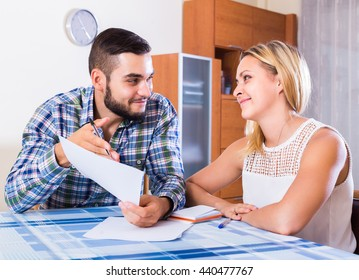Happy young couple at the table filling forms for joint banking account