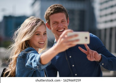 Happy young couple taking photo together using smartphone in city