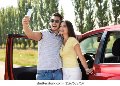 Happy young couple taking selfie near car on road