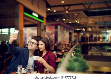 Happy young couple taking selfie with smart phone at cafe in mall. Copy space for your text. Shallow depth of field. Very useful photo for processing with one click on edit image.