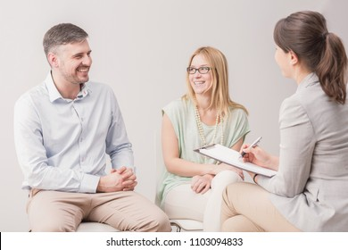 Happy, young couple talking to a clerk in civil registry office, preparing for their wedding