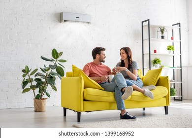 happy young couple talking and holding cups while sitting on yellow sofa under air conditioner at home