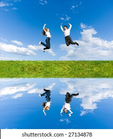 Happy Young Couple - team is jumping in the sky above a green meadow