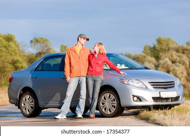 Happy young couple with their new car.