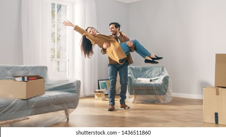 Happy Young Couple in Their Newly Purchased / Rented Apartment, Boyfriend Carries His Girlfriend. Contemporary Bright Home for Modern Young People.
