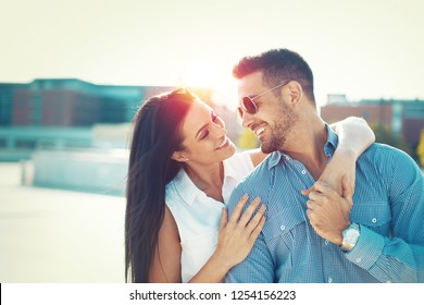 Happy young couple toothy smiling each other and embracing outdoor in sunset